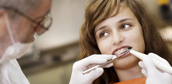 An orthodontist examining dental braces of a patient